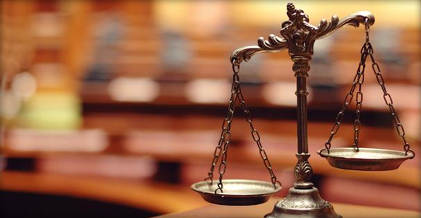 decorative photo of scales of law in front of blurred background