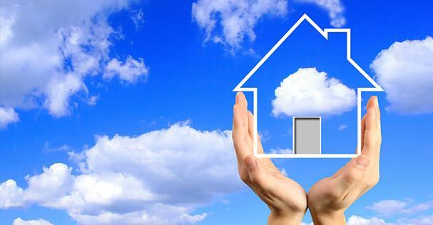 decorative hands holding photo of house outline in clouds